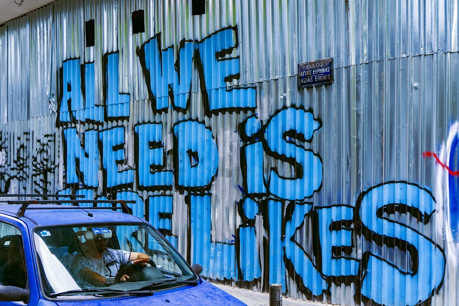 "Social media graffiti on a wall in Athens, Greece, reading, ""All we need is more likes"""
